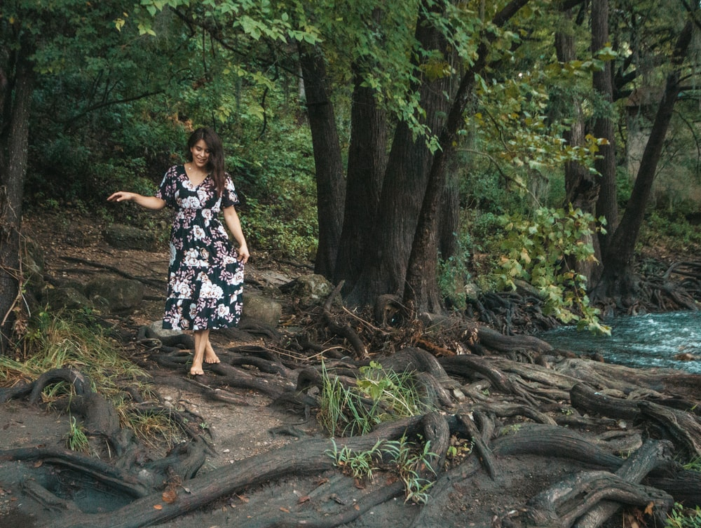 woman in black and white floral dress standing on brown tree log during daytime