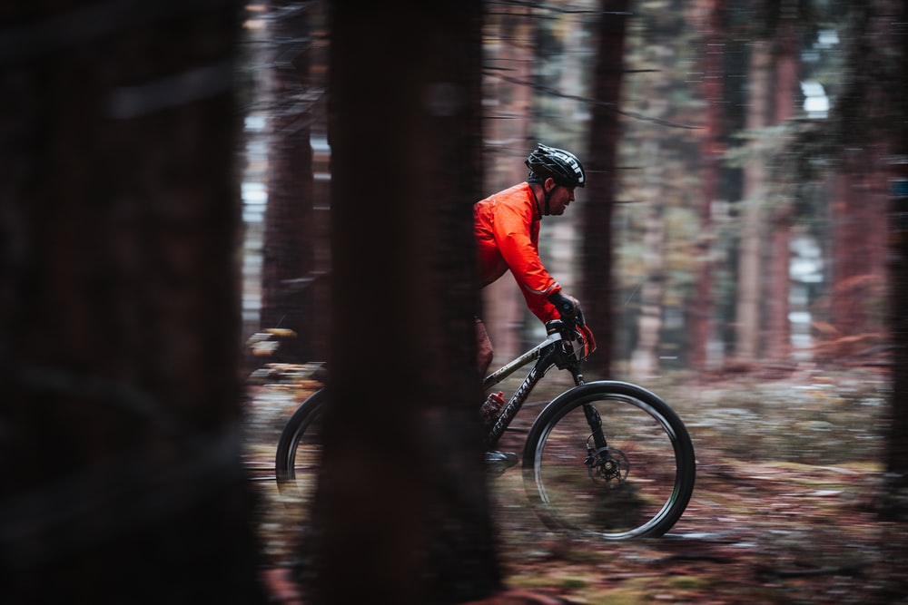 man in red jacket riding bicycle in forest during daytime