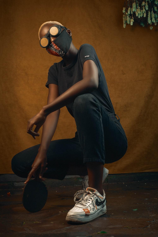 woman in black tank top and black pants sitting on brown wooden floor