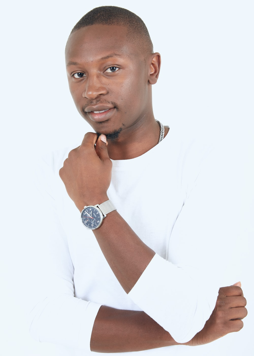 man in white crew neck t-shirt wearing silver round analog watch