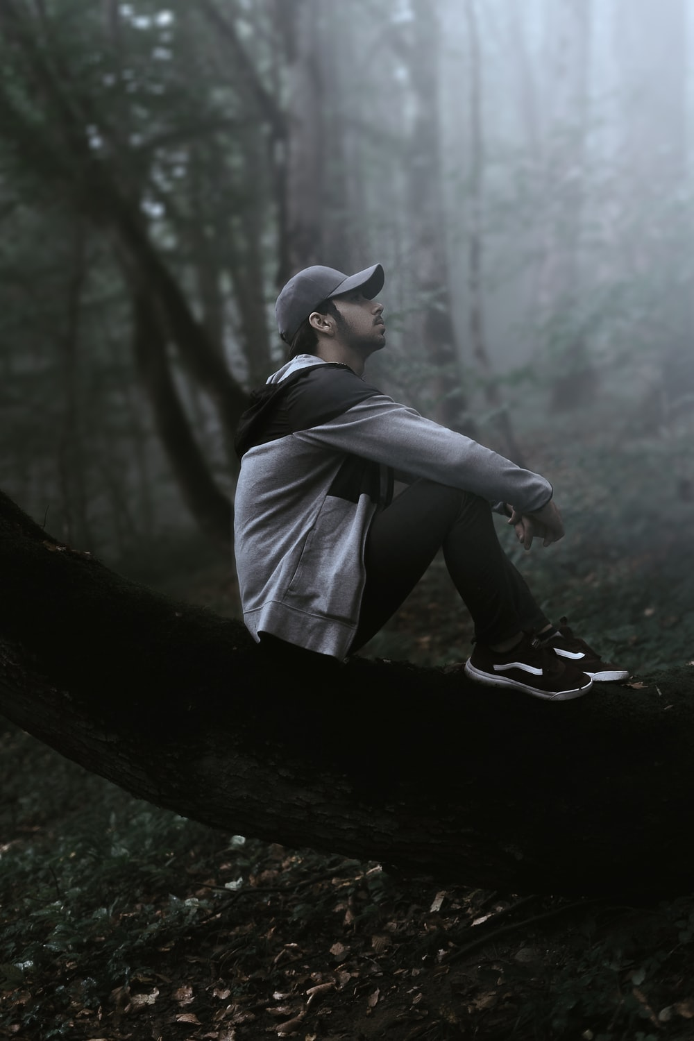 man in black leather jacket and black hat sitting on tree log