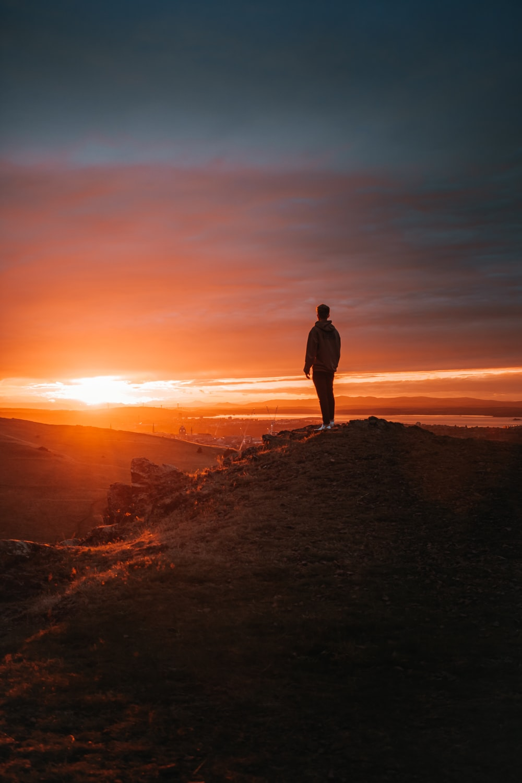 man in black jacket standing on brown rock during sunset