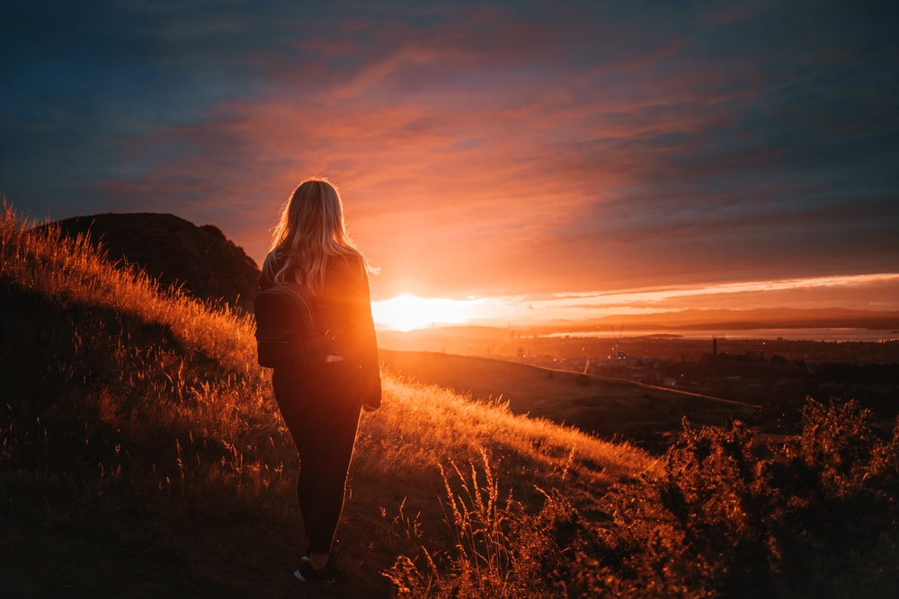 woman in black jacket standing on grass field during sunset
