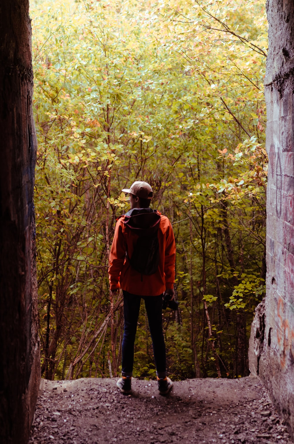 man in red jacket and black pants standing in the middle of forest during daytime