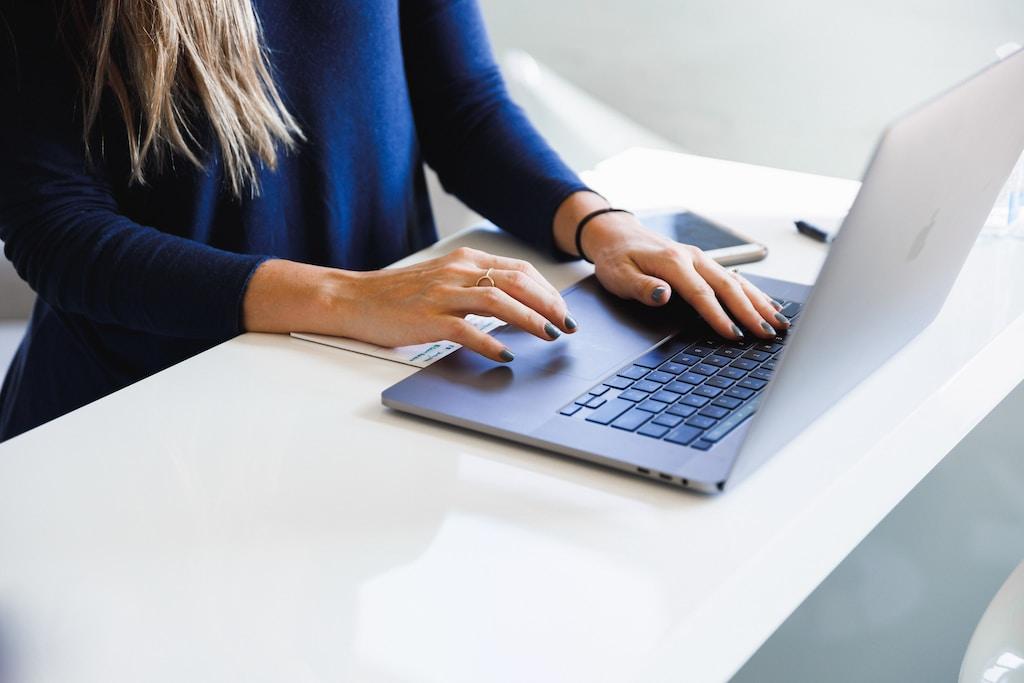 woman in blue long sleeve shirt using macbook pro