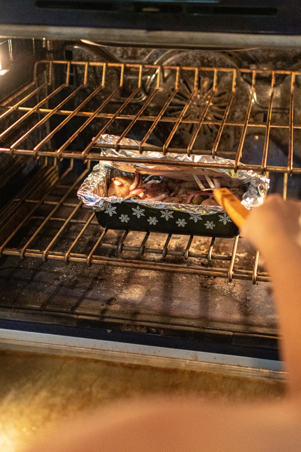person holding grilled meat on black tray