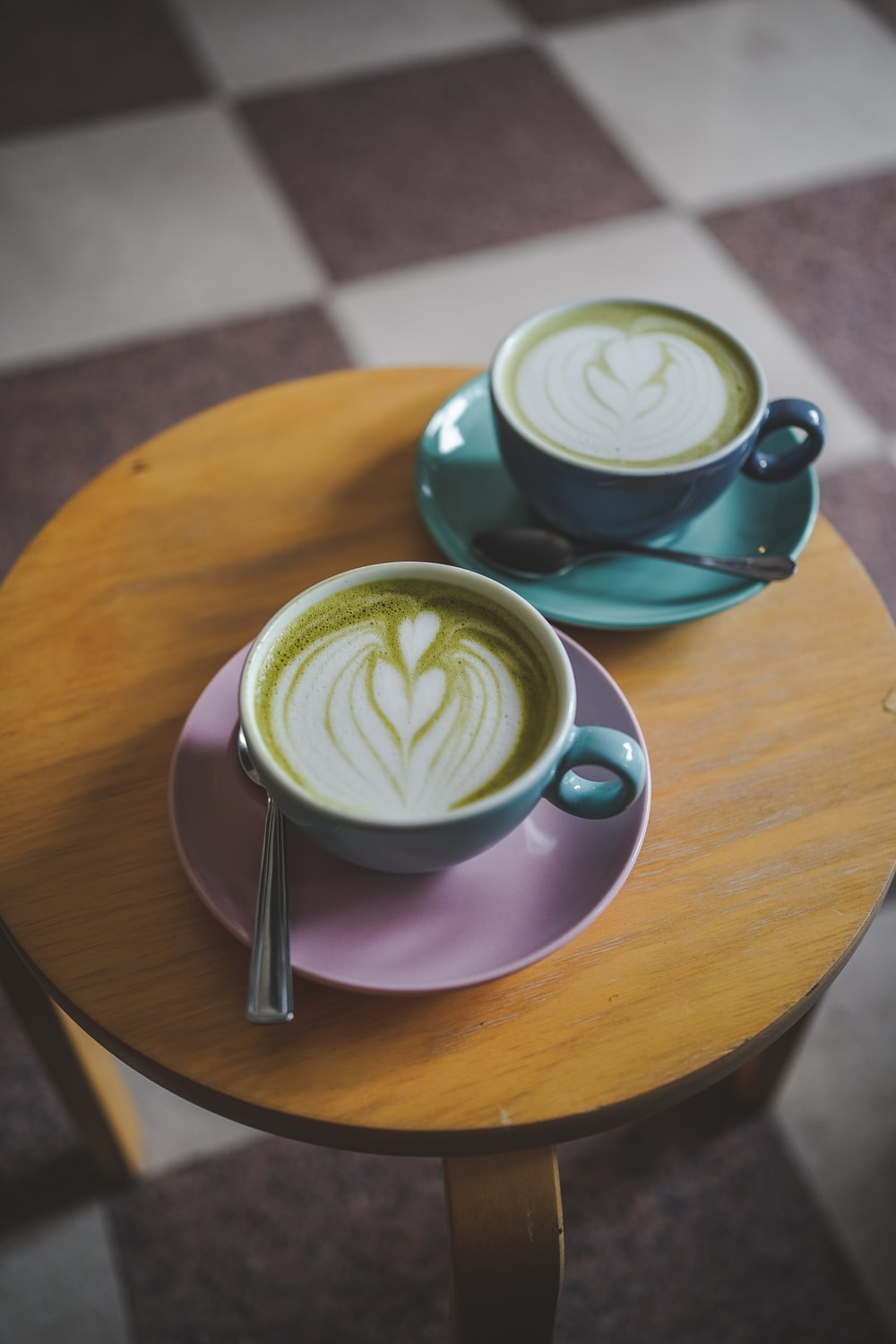 green and white ceramic cup with saucer on brown wooden table
