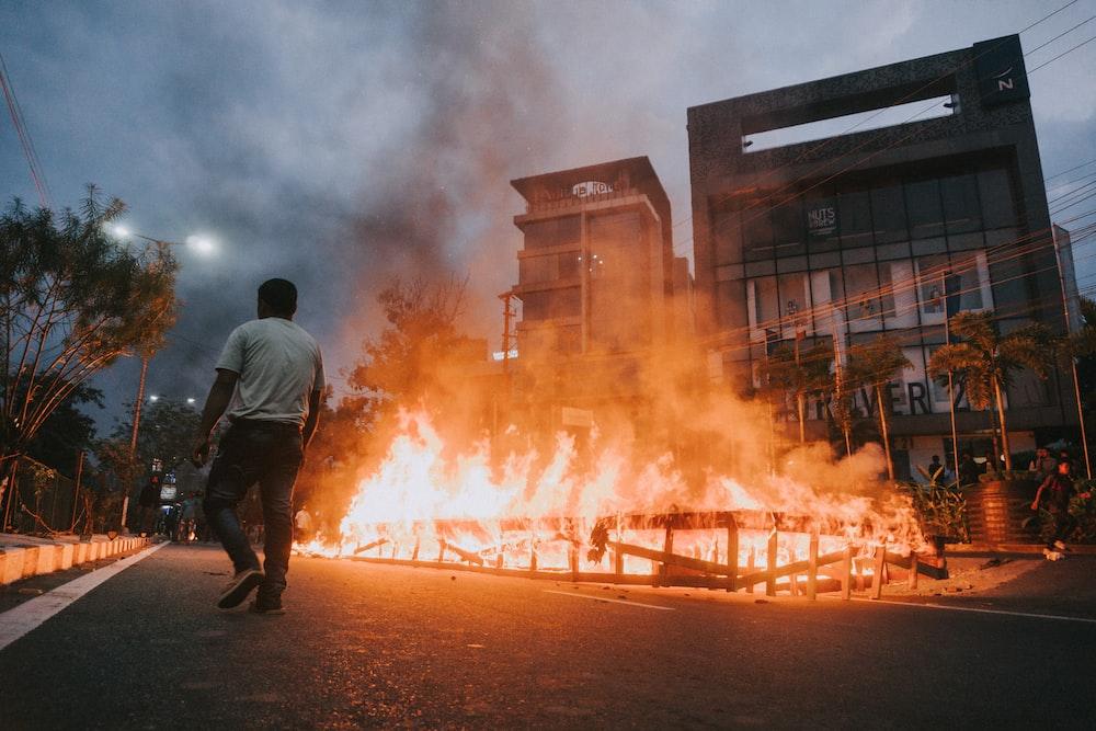 man in black jacket standing near burning building