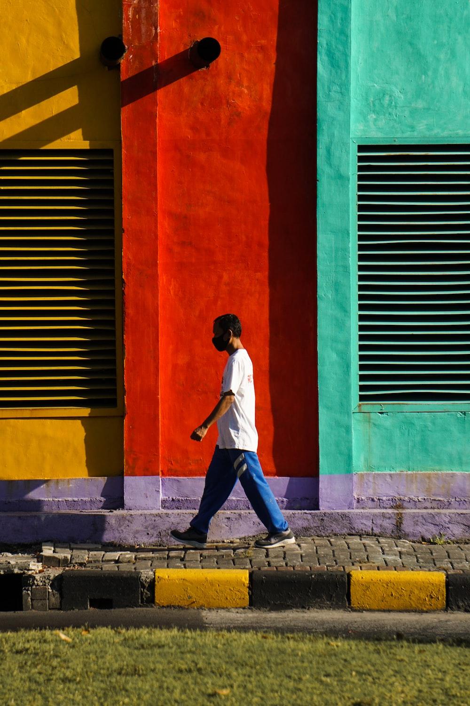 man in white long sleeve shirt and blue denim jeans walking on sidewalk during daytime