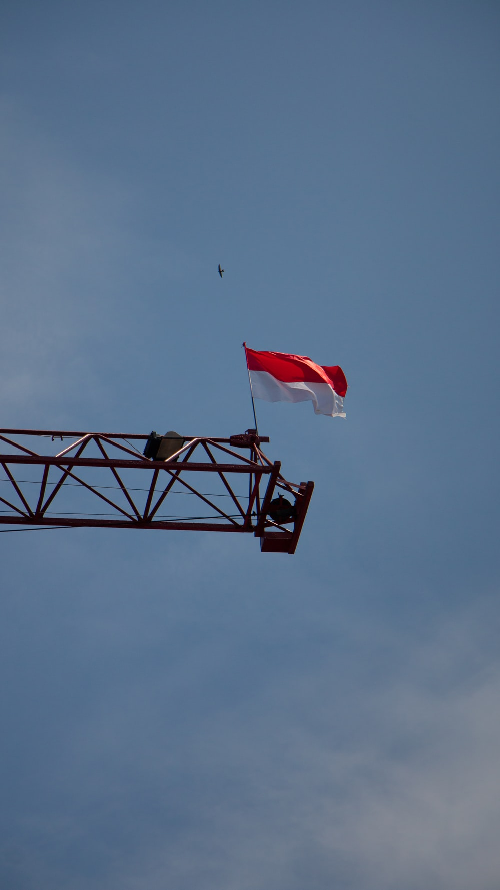 white and red flag on black metal pole under blue sky during daytime