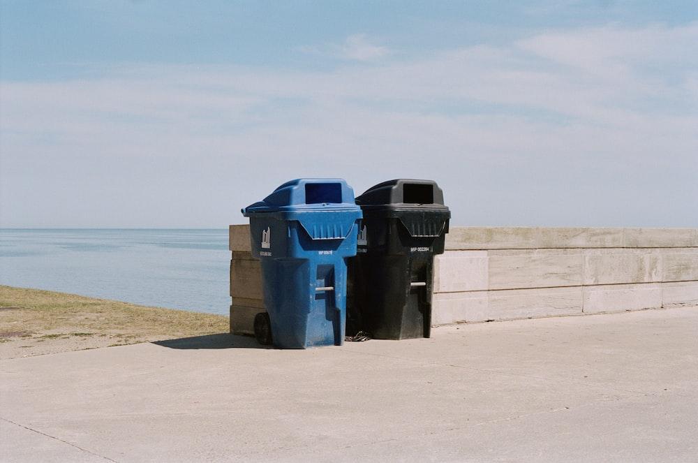 blue trash bin on beach during daytime
