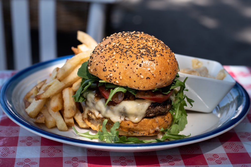 burger with lettuce and tomatoes on white ceramic plate