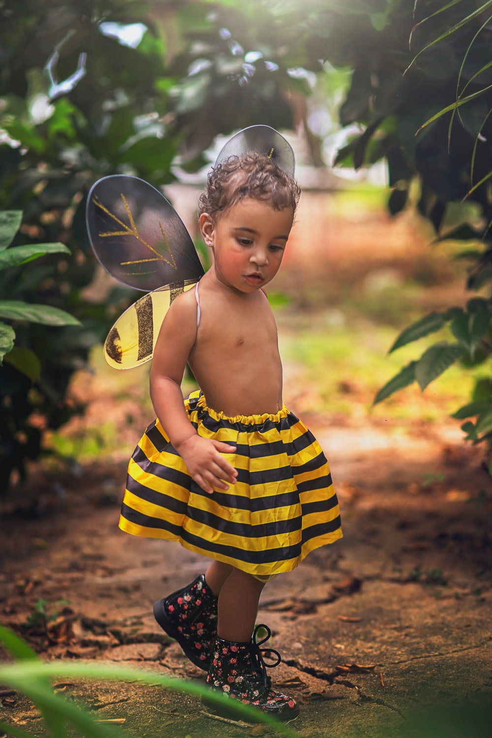 girl in yellow and black stripe dress standing near green leaf tree during daytime