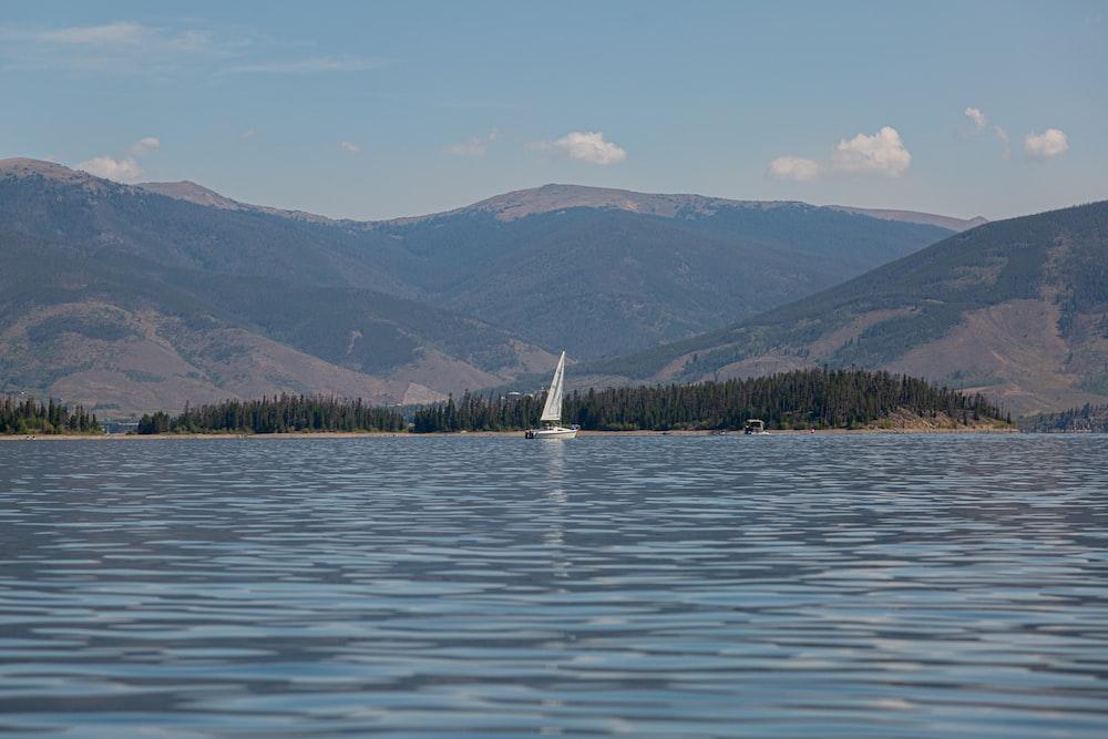 white sailboat on sea near green mountains during daytime