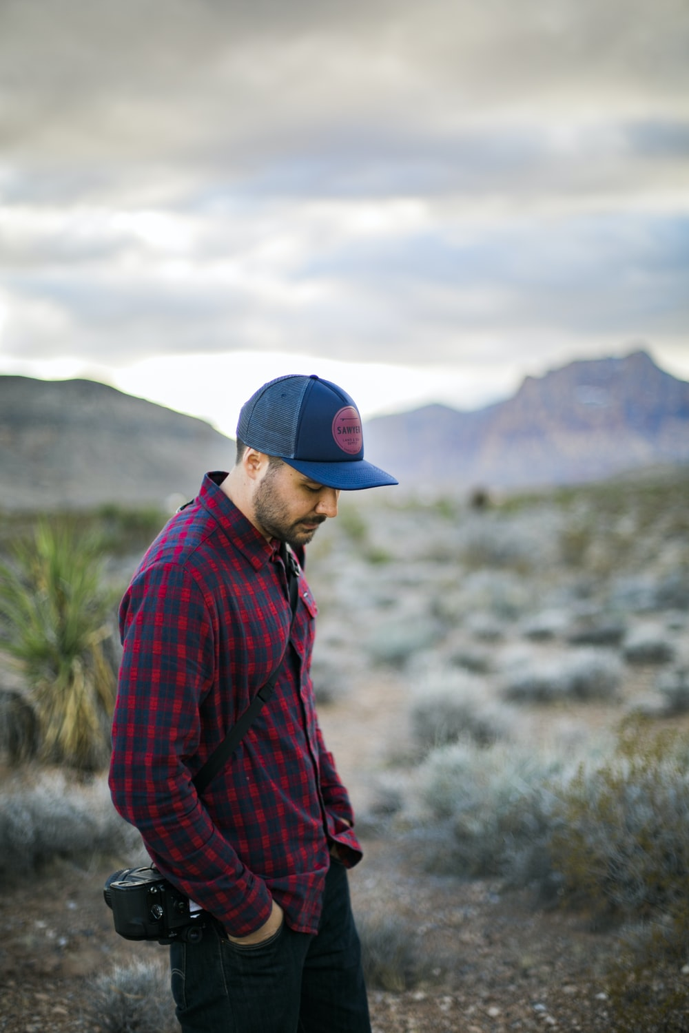 man in red and black plaid dress shirt and blue fitted cap standing on green grass
