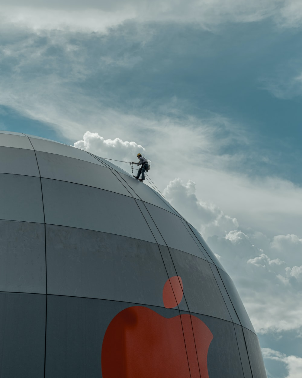 man in black jacket riding bicycle on brown round building under white clouds during daytime