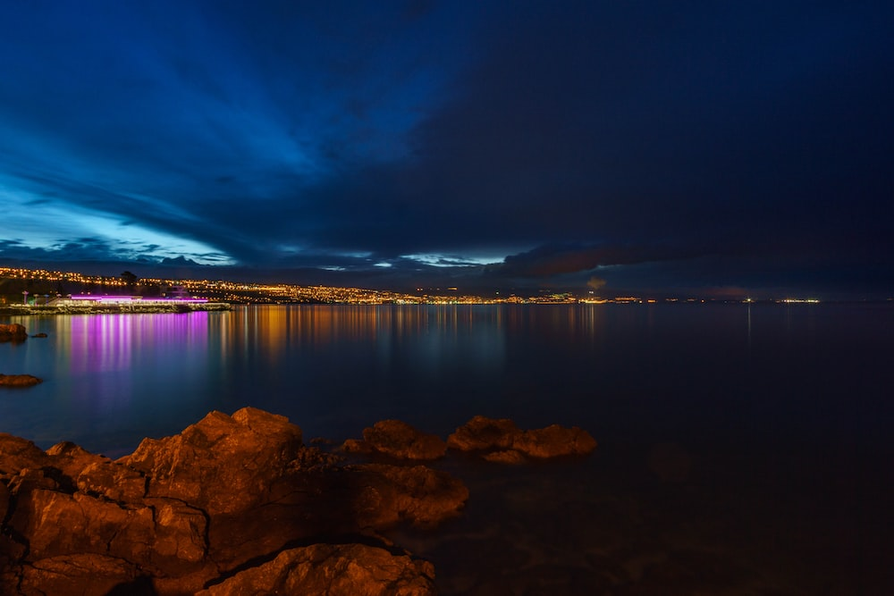 body of water near mountain during night time