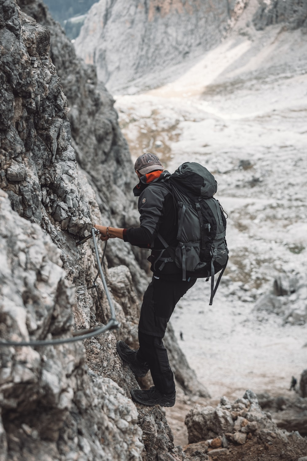 man in black jacket and black pants with black backpack climbing on brown rock mountain during