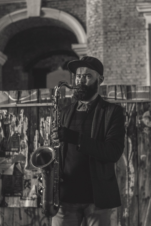 man in black jacket playing saxophone