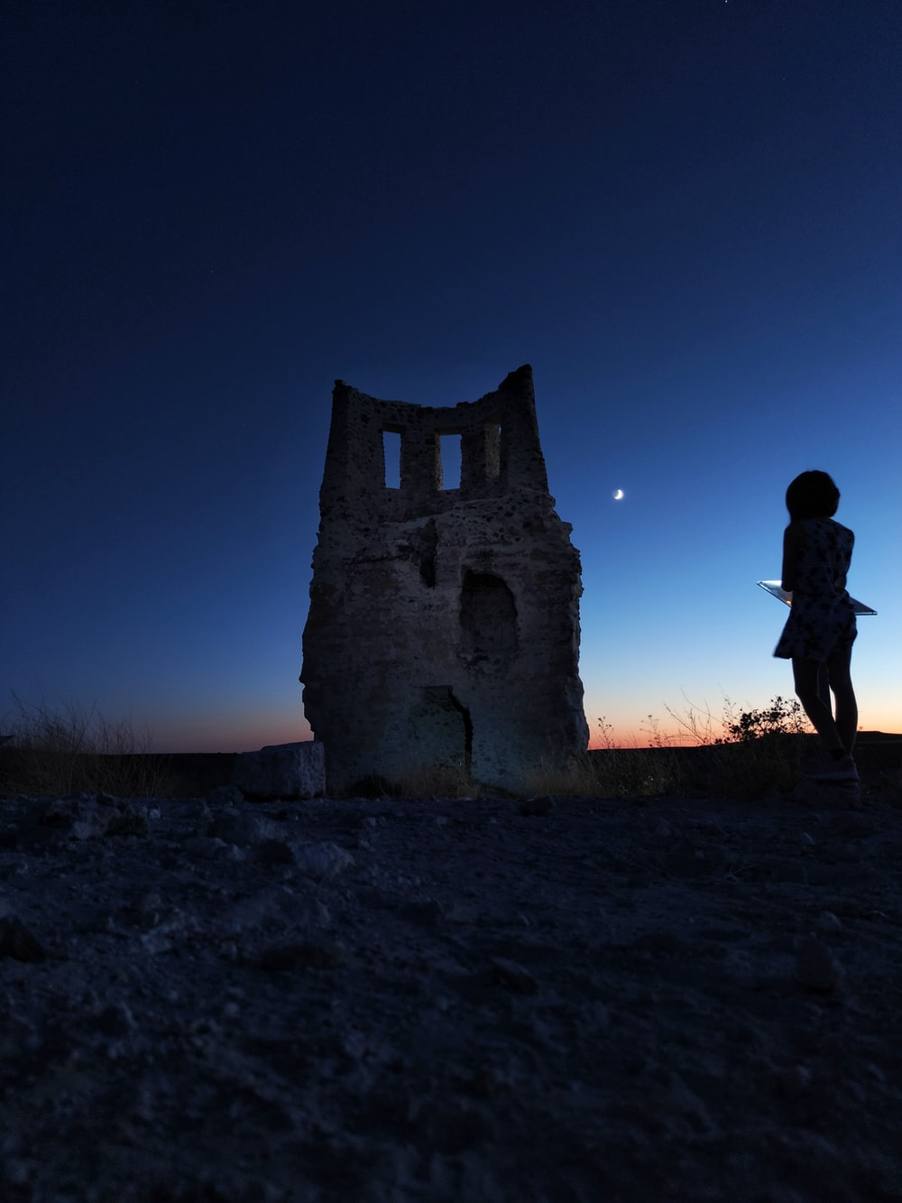 silhouette of woman standing near brown concrete building during night time