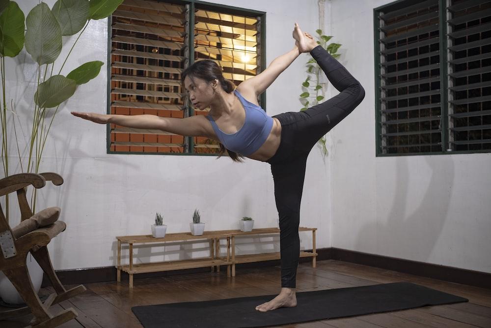 woman in blue sports bra and black leggings doing yoga