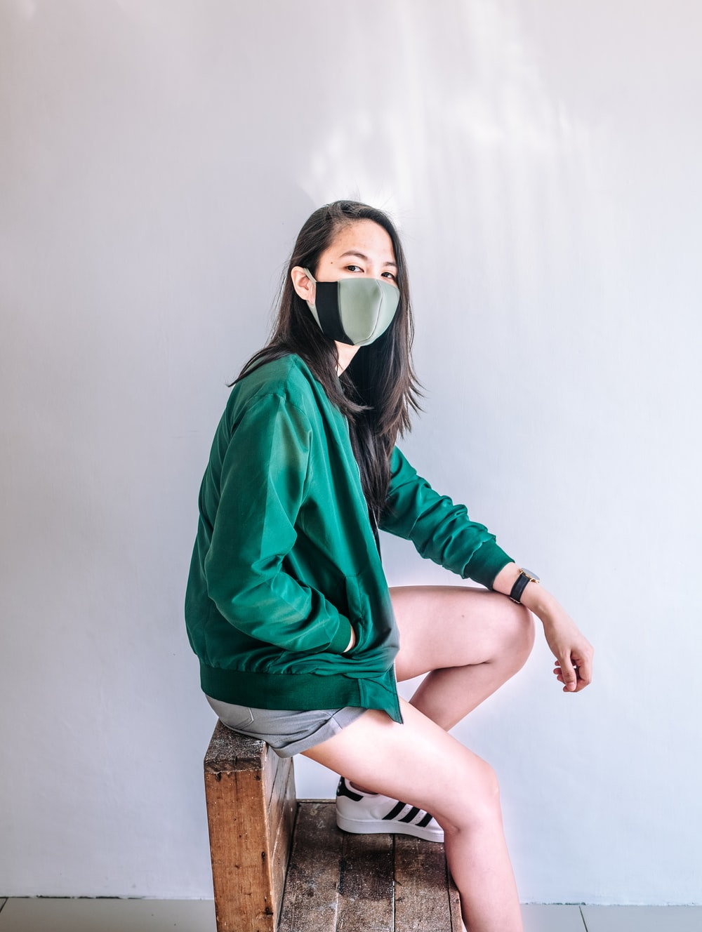 woman in green jacket and brown denim shorts wearing white goggles