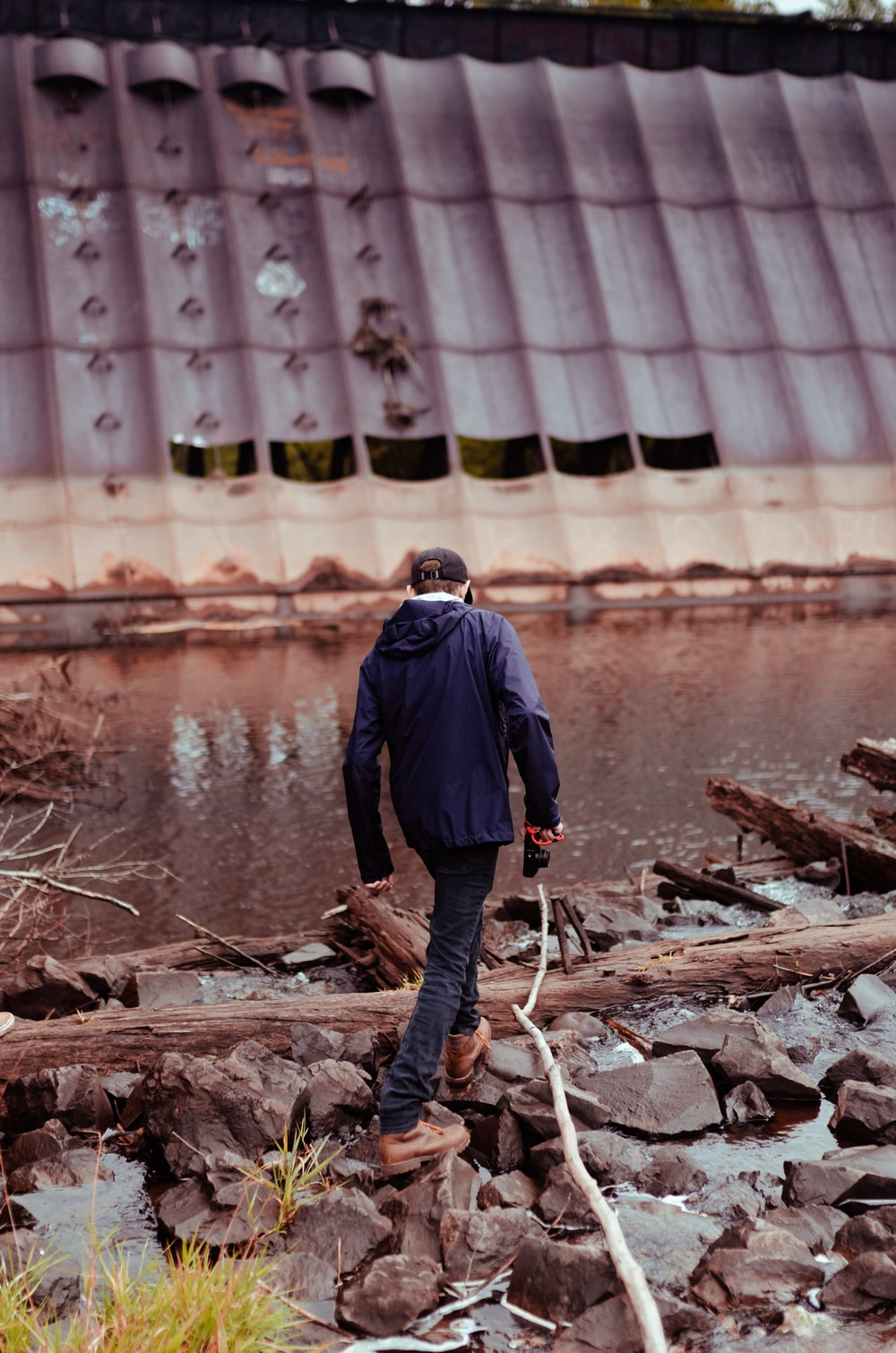 man in blue jacket and black pants standing on brown wood log near body of water