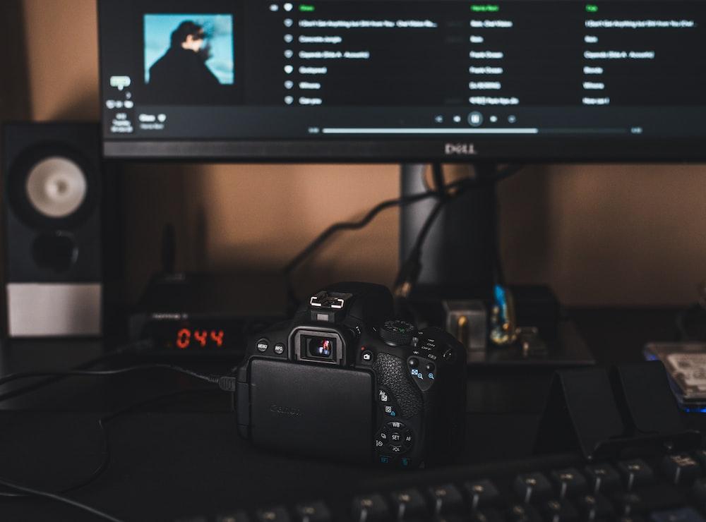 black canon dslr camera on black computer keyboard