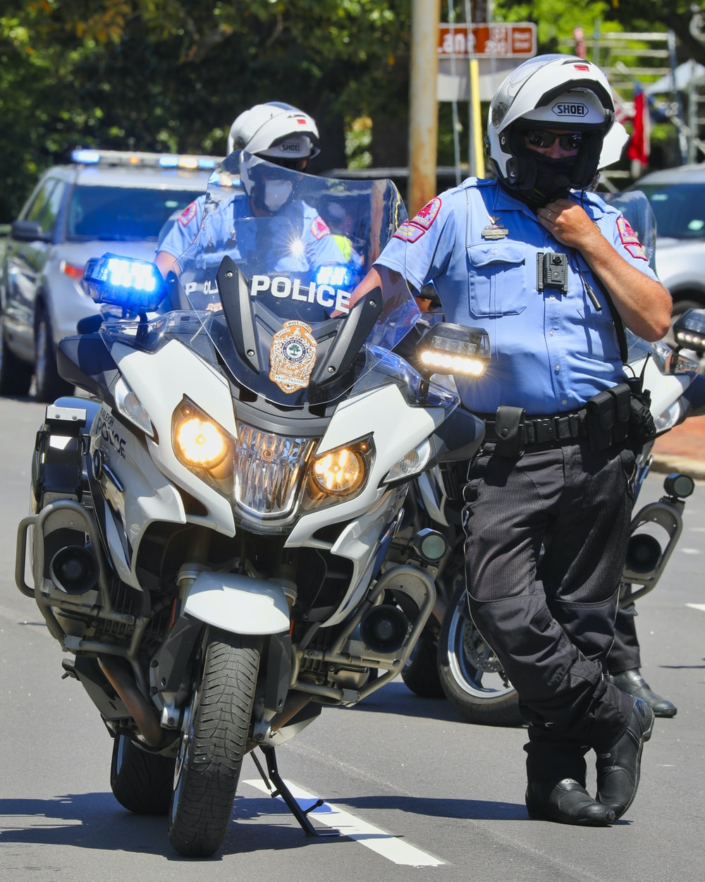 man in blue and white police suit riding on blue and white motorcycle during daytime