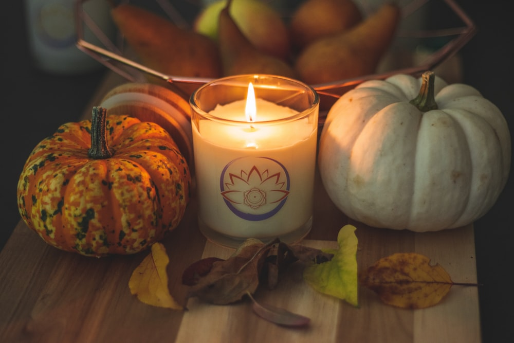 white pillar candle beside white and brown pumpkin