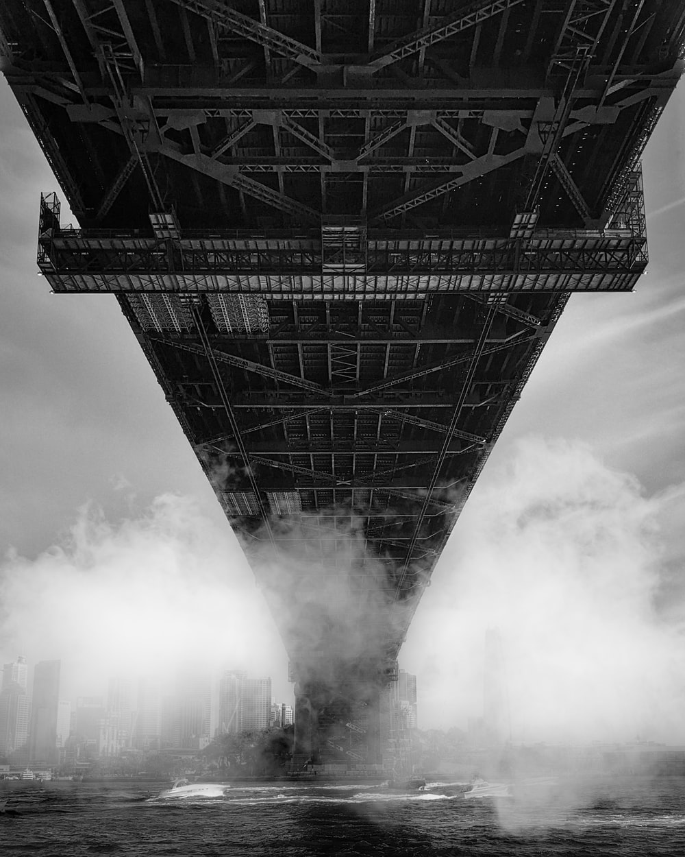 grayscale photo of smoke coming from a bridge
