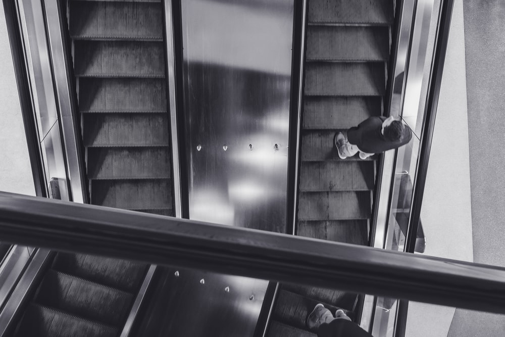 grayscale photo of man in black jacket and pants sitting on stairs