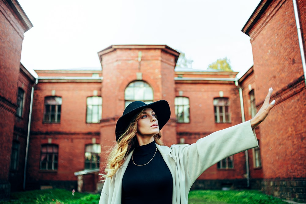 woman in white long sleeve shirt and black hat standing near brown concrete building during daytime