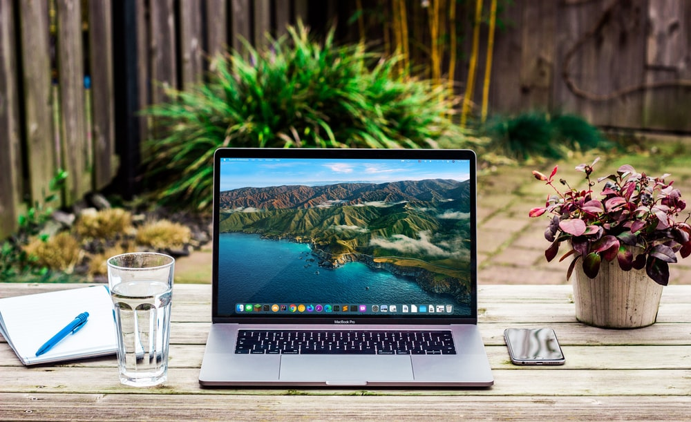 macbook pro beside clear drinking glass on brown wooden table