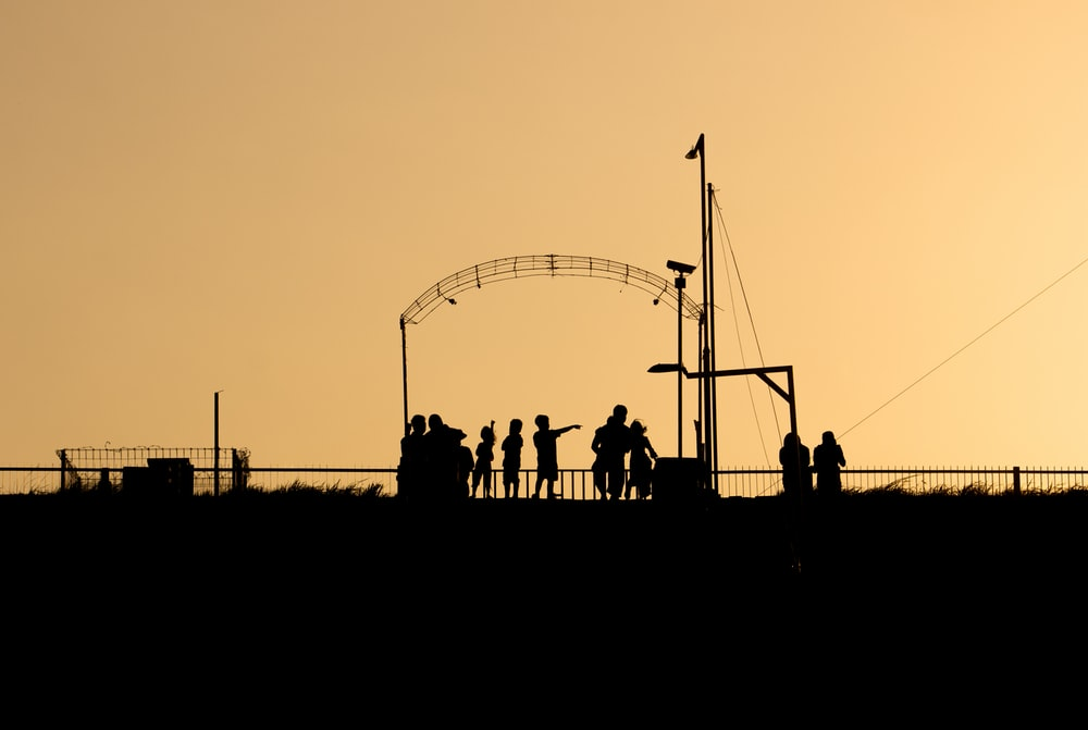 silhouette of people standing near ferris wheel during sunset