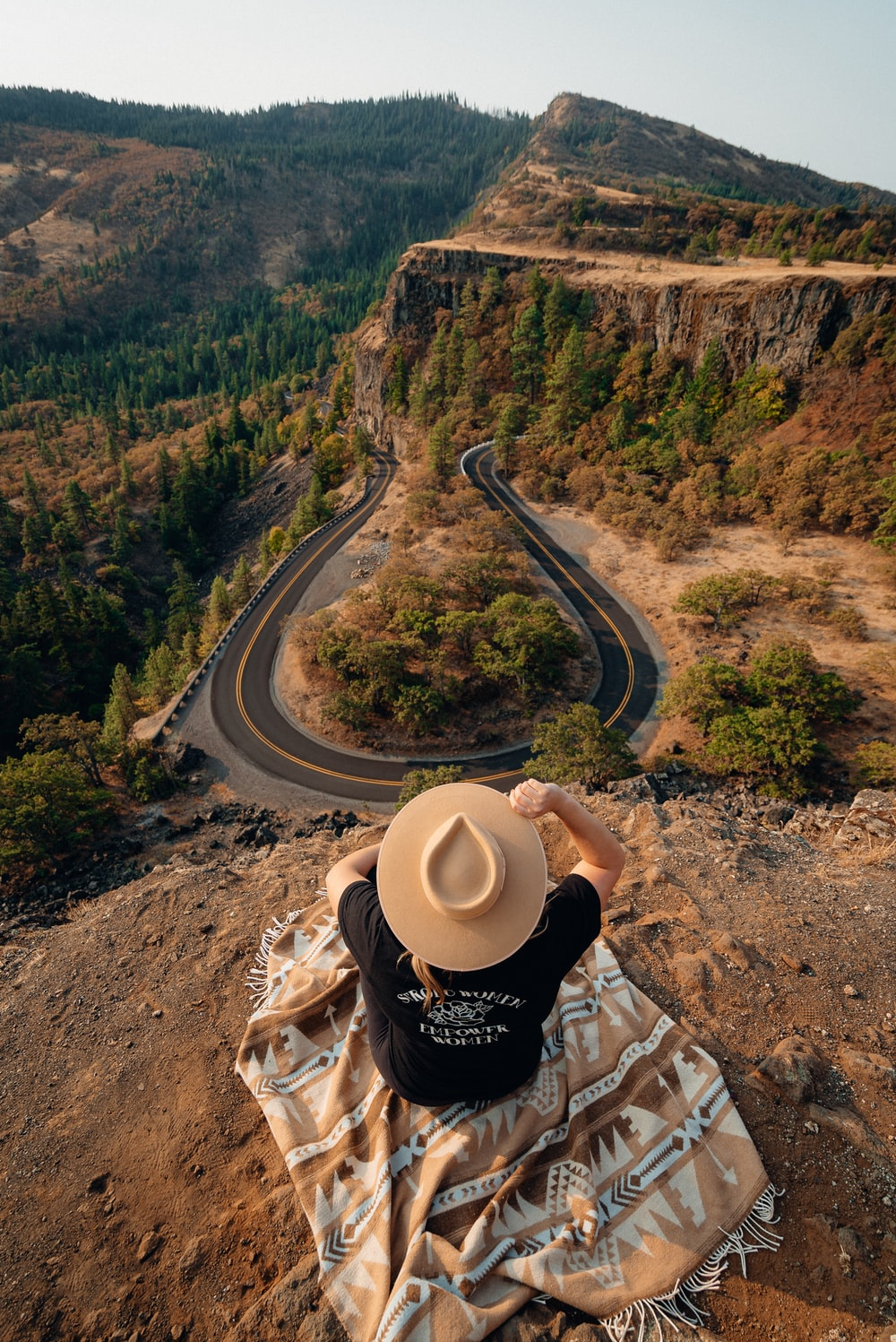 person in black and white long sleeve shirt and beige cowboy hat sitting on brown rock