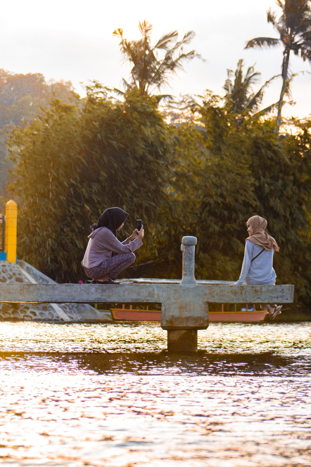 man and woman sitting on bench near body of water during daytime