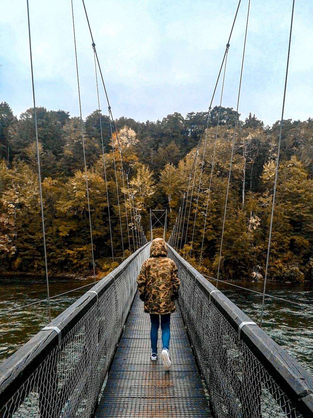 woman in blue shirt and blue denim jeans walking on hanging bridge