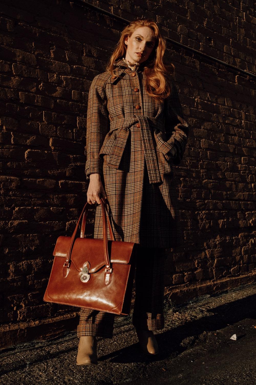 woman in brown coat holding brown leather handbag