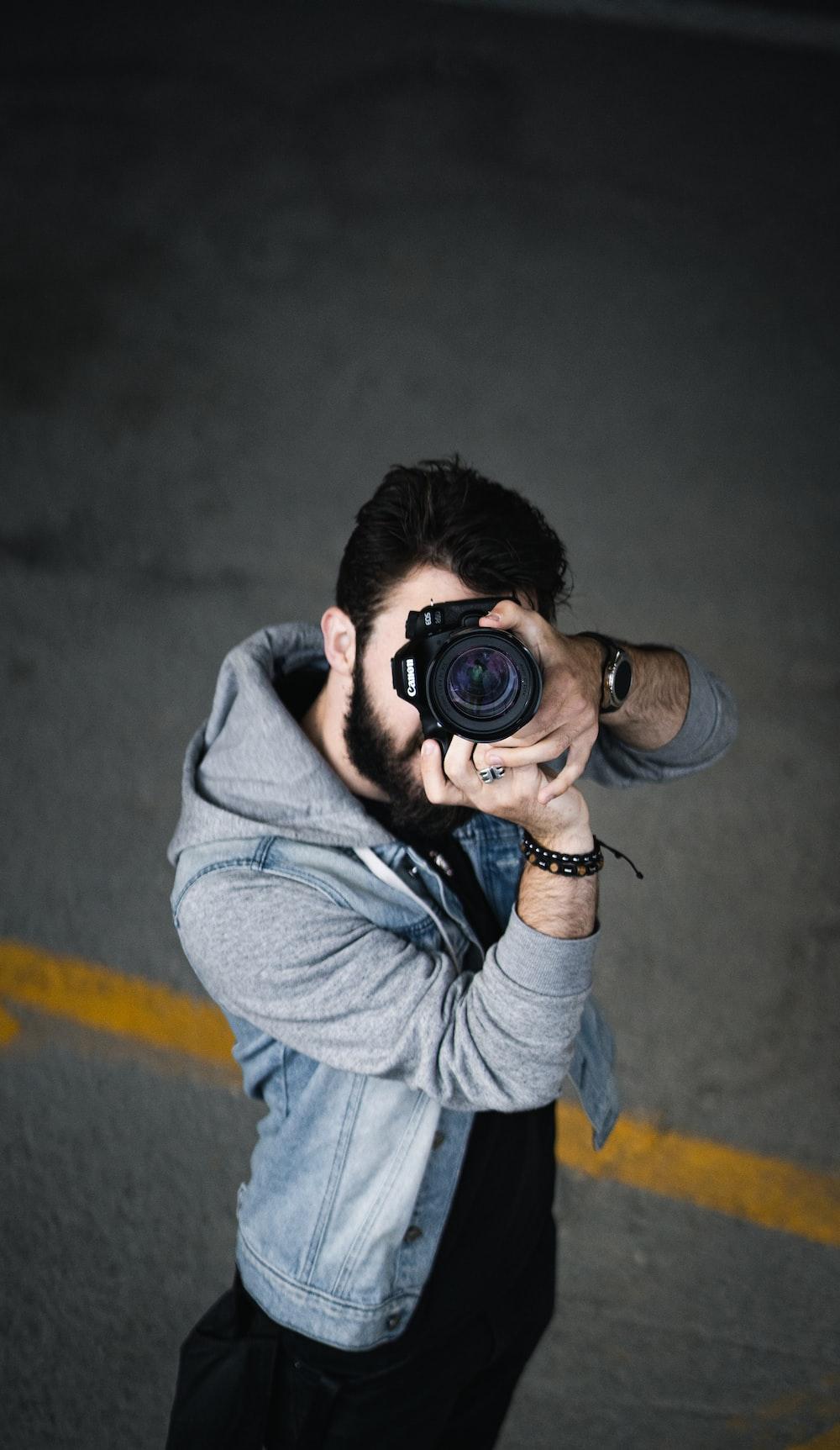 man in gray hoodie holding black dslr camera