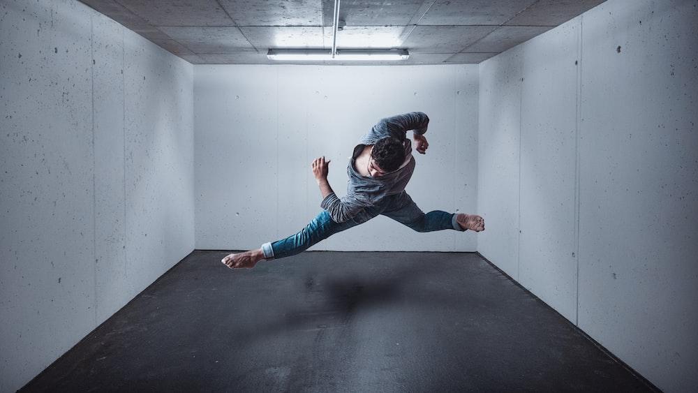 girl in blue denim jeans and black jacket jumping on black floor