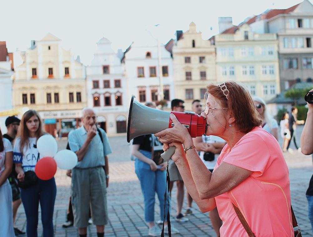 woman in pink shirt kissing man in black shirt during daytime
