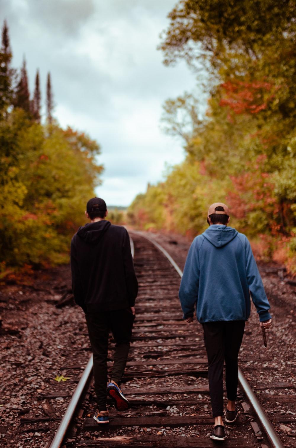man in gray hoodie walking on pathway during daytime