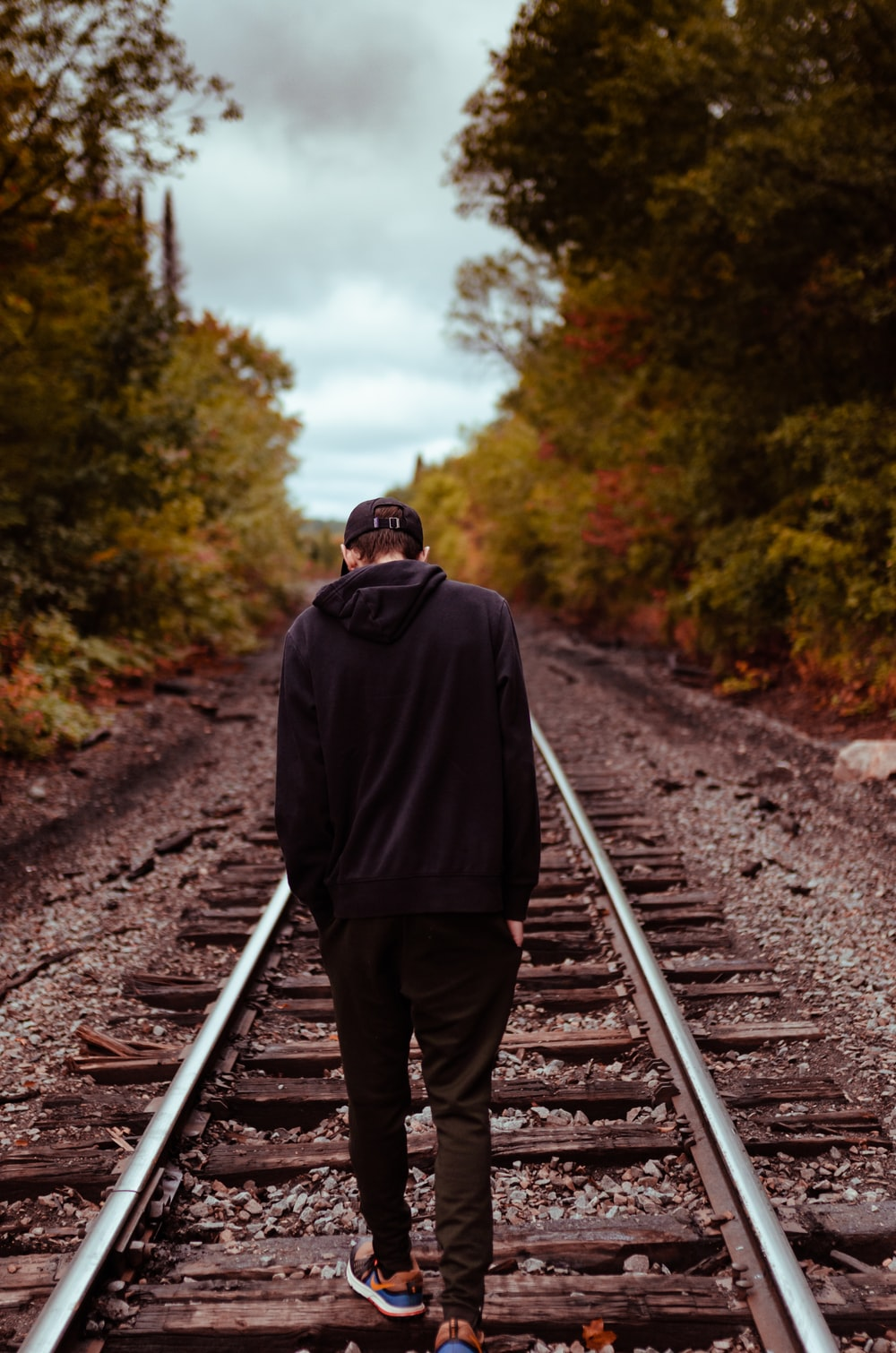 man in black hoodie and brown pants standing on train rail during daytime