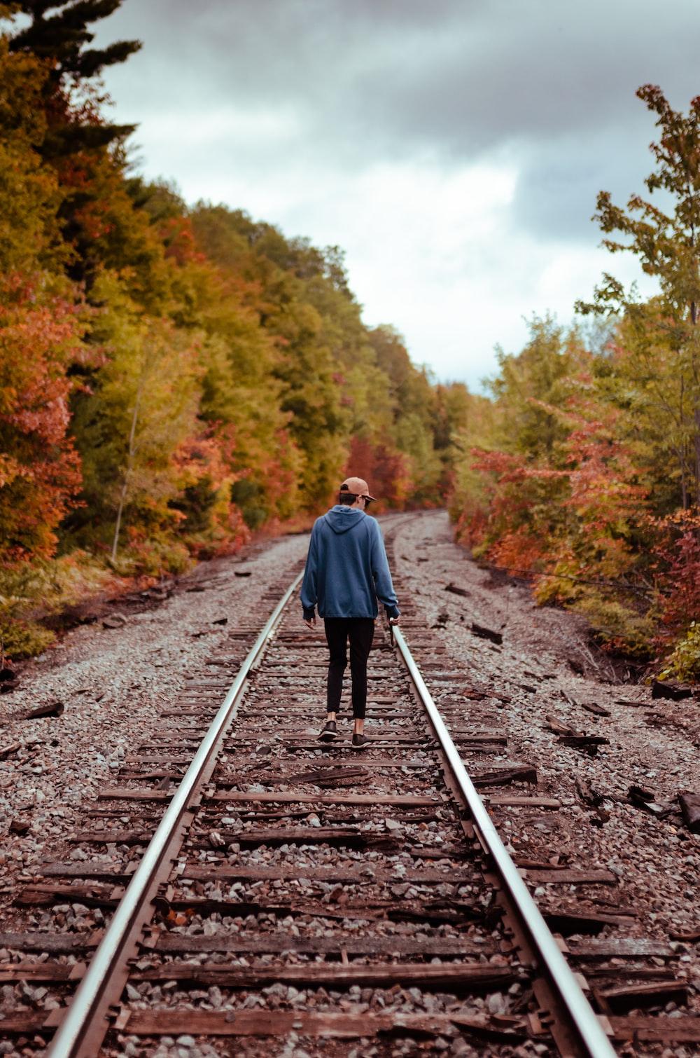 woman in blue hoodie walking on train rail during daytime