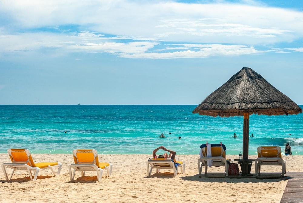 brown beach umbrellas on beach during daytime