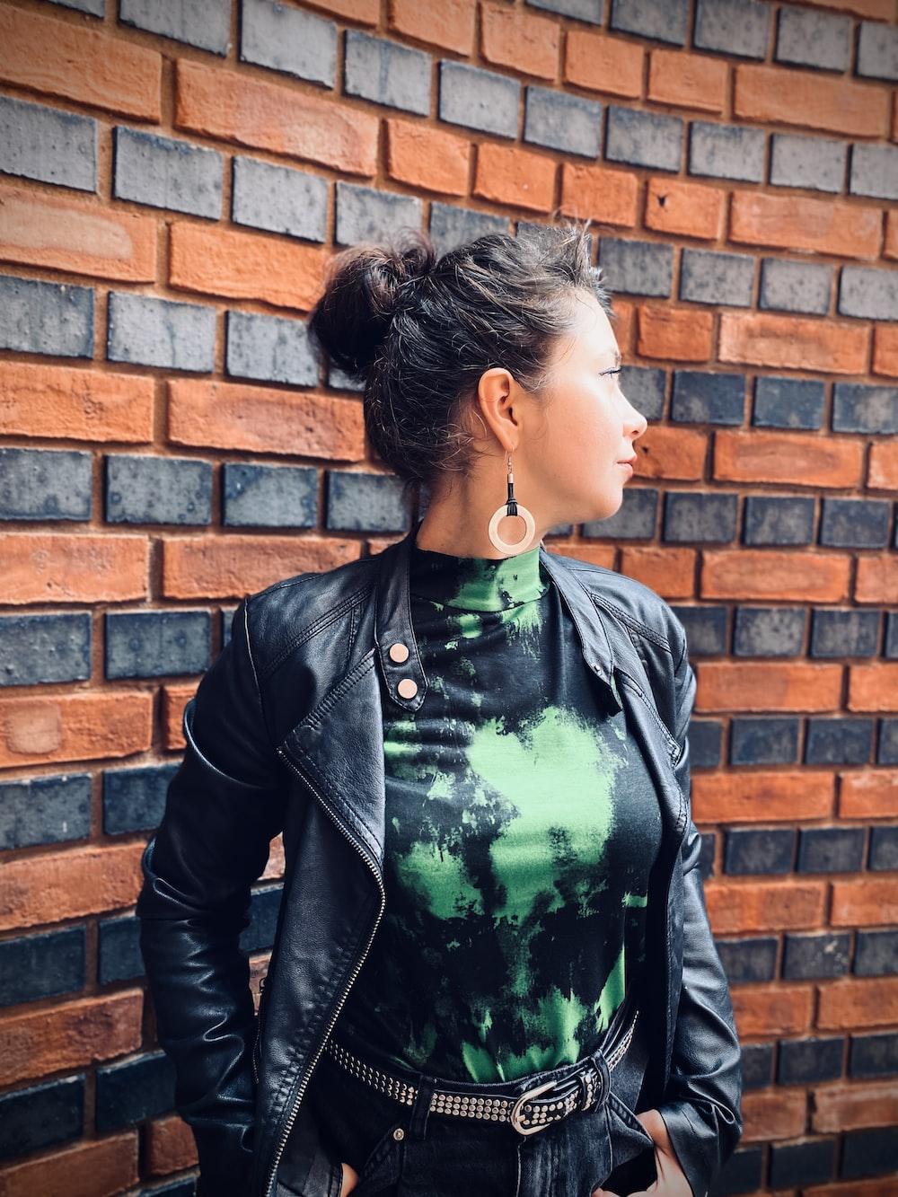 woman in black leather jacket standing beside brown brick wall