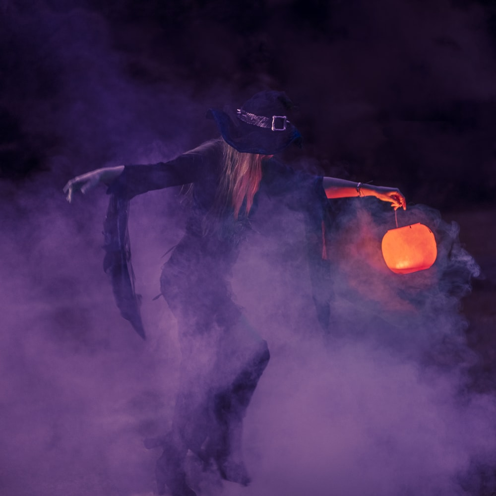 woman in black long sleeve shirt and black hat standing on black smoke