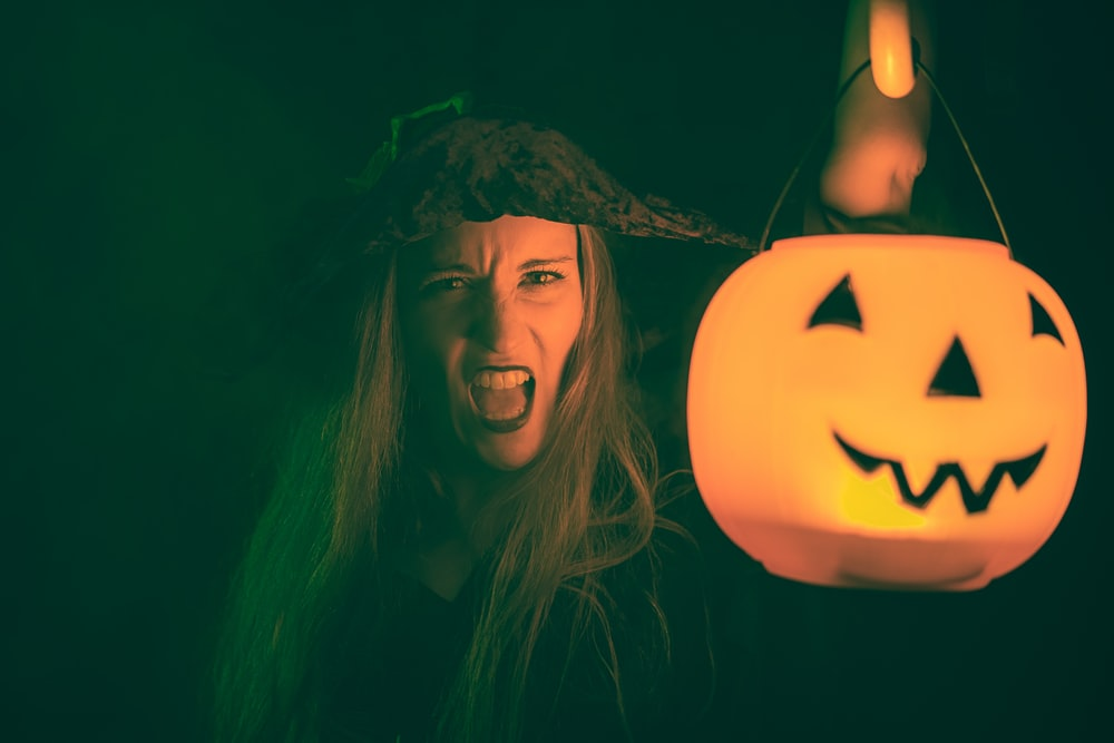 woman with black hair holding jack o lantern