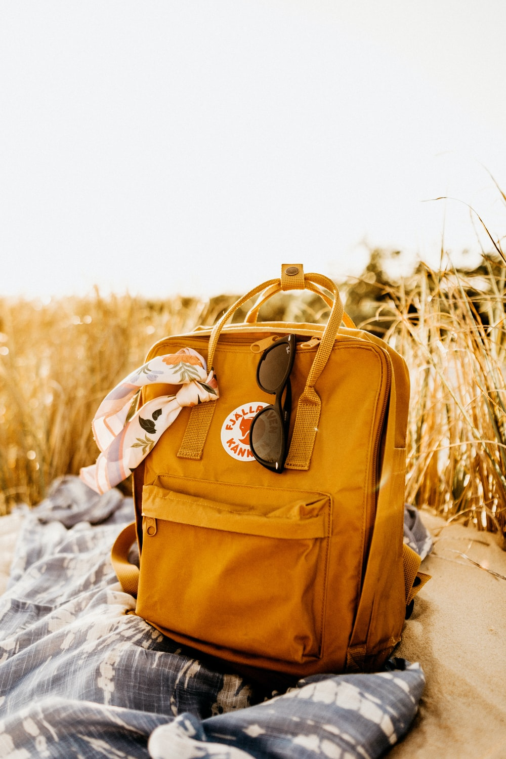 brown leather backpack on snow covered ground during daytime